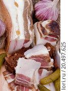 Купить «Arrangement of Sliced Raw Smoked Homemade Bacon, Garlic, Brown Bread and Marinated Gherkins closeup on Cutting Board», фото № 20497625, снято 3 января 2013 г. (c) easy Fotostock / Фотобанк Лори