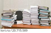 Купить «Рабочий стол офисного работника с большим стопками бумаг», эксклюзивное фото № 20715589, снято 18 января 2016 г. (c) Владимир Чинин / Фотобанк Лори