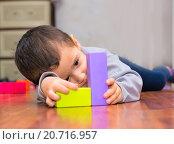 Купить «Мальчик лежа играет с кубиками», фото № 20716957, снято 15 января 2016 г. (c) Назарова Мария / Фотобанк Лори