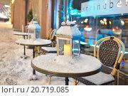 Купить «Свеча горит на заснеженном столике уличного летнего кафе зимним вечером», фото № 20719085, снято 9 января 2016 г. (c) Валерия Попова / Фотобанк Лори