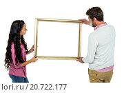 Купить «Smiling couple holding picture frame», фото № 20722177, снято 28 мая 2015 г. (c) Wavebreak Media / Фотобанк Лори