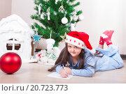 Купить «Девочка семи лет в красной шапке лежа пишет письмо для Деда Мороза», фото № 20723773, снято 14 января 2016 г. (c) Emelinna / Фотобанк Лори