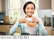 Купить «Smiling brunette holding mug», фото № 20732421, снято 15 июля 2015 г. (c) Wavebreak Media / Фотобанк Лори