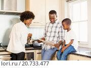 Купить «Family reading in the kitchen», фото № 20733477, снято 15 июля 2015 г. (c) Wavebreak Media / Фотобанк Лори