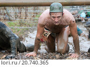 Купить «A contestant negotiates his way under barbed wire during The Tough Guy contest.», фото № 20740365, снято 26 января 2014 г. (c) age Fotostock / Фотобанк Лори