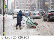 Гастарбайтер высыпает снег из тачки на парковку на ул.Петровка после отъезда полицейского автомобиля (2016 год). Редакционное фото, фотограф Александр Михайловский / Фотобанк Лори