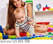 Купить «Baby boy playing with her young beautiful mother.», фото № 21091189, снято 28 сентября 2015 г. (c) Gennadiy Poznyakov / Фотобанк Лори