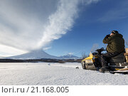 Фотограф снимает Ключевской вулкан сидя на снегоходе (2016 год). Редакционное фото, фотограф А. А. Пирагис / Фотобанк Лори