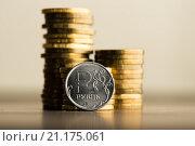 Купить «Российский рубль и стопки золотых монет на столе», фото № 21175061, снято 22 января 2015 г. (c) Валерия Потапова / Фотобанк Лори