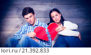 Composite image of young couple sitting on floor with broken heart. Стоковое фото, агентство Wavebreak Media / Фотобанк Лори