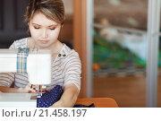Купить «Девушка сидит за столом и шьет на швейной машинке», фото № 21458197, снято 26 января 2016 г. (c) Евгений Майнагашев / Фотобанк Лори