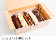 Эклеры, торты в картонной коробке на белом фоне. Стоковое фото, фотограф Riasna Yuliia / Фотобанк Лори