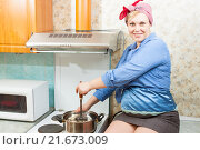 Купить «Улыбающаяся беременная женщина готовит суп, сидя рядом с плитой», фото № 21673009, снято 10 апреля 2015 г. (c) Сергей Дубров / Фотобанк Лори