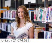 Купить «Happy female student holding books at the library», фото № 21674625, снято 25 ноября 2014 г. (c) Sergey Nivens / Фотобанк Лори