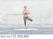 Купить «woman making yoga in tree pose on mat», фото № 21703909, снято 13 ноября 2015 г. (c) Syda Productions / Фотобанк Лори