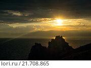 Закат на берегу острова Ольхон (озеро Байкал) с чайками, летящими над скалой Шаманкой. Стоковое фото, фотограф Иван Рочев / Фотобанк Лори