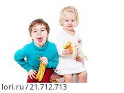 Купить «Мальчик и девочка едят бананы», фото № 21712713, снято 23 декабря 2015 г. (c) Ирина Мойсеева / Фотобанк Лори