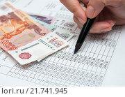 Купить «Девушка подсчитывает сумму оплаты в графике платежей кредитного договора», эксклюзивное фото № 21741945, снято 8 февраля 2016 г. (c) Игорь Низов / Фотобанк Лори