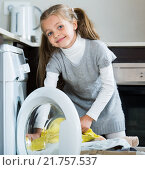 Купить «Little girl unloading washing machine and smiling», фото № 21757537, снято 5 декабря 2019 г. (c) Яков Филимонов / Фотобанк Лори