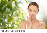 young woman applying lip balm to her lips. Стоковое фото, фотограф Syda Productions / Фотобанк Лори