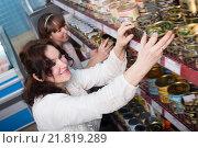 Купить «Happy female customers selecting tinned products», фото № 21819289, снято 7 декабря 2019 г. (c) Яков Филимонов / Фотобанк Лори