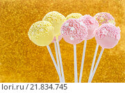 Купить «Pink and yellow cake pops decorated with sprinkles. Gold glittering background», фото № 21834745, снято 23 марта 2019 г. (c) BE&W Photo / Фотобанк Лори