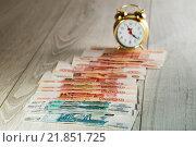 Купить «Деньги - время. Денежные купюры образуют дорожку к часам», эксклюзивное фото № 21851725, снято 16 февраля 2016 г. (c) Юрий Шурчков / Фотобанк Лори