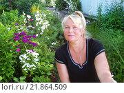 Улыбающаяся женщина ухаживает за цветами. Стоковое фото, фотограф Юрий Морозов / Фотобанк Лори