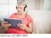 Купить «Happy senior woman listening to music», фото № 21881993, снято 10 ноября 2015 г. (c) Wavebreak Media / Фотобанк Лори