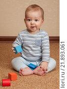 Ребенок сидит на полу и играет с кубиками. Стоковое фото, фотограф Ирина Столярова / Фотобанк Лори