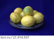 Лимоны на терелке на синем фоне. Стоковое фото, фотограф Лидия Хвесюк / Фотобанк Лори