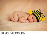 Новорожденный на животе в черно-желтой шапочке. Стоковое фото, фотограф Елена Ганненко / Фотобанк Лори