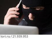 Хакер в маске сидит за ноутбуком и говорит по мобильному. Стоковое фото, фотограф Mark Agnor / Фотобанк Лори
