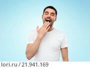 Купить «tired sleepy yawning man over blue background», фото № 21941169, снято 15 января 2016 г. (c) Syda Productions / Фотобанк Лори