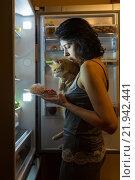 Женщина ночью у открытого холодильника с котом на руках. Стоковое фото, фотограф Okssi / Фотобанк Лори