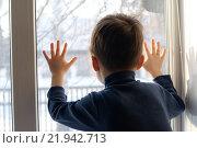 Мальчик в ожидании смотрит в окно. Стоковое фото, фотограф Айнур Шауэрман / Фотобанк Лори
