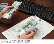 Купить «Кассир выдаёт заработную плату на фоне трудового договора», эксклюзивное фото № 21971829, снято 25 февраля 2016 г. (c) Игорь Низов / Фотобанк Лори