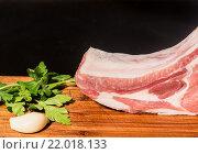 Сочный кусок мяса на кости с чесноком лежат на деревянном столе. Стоковое фото, фотограф Riasna Yuliia / Фотобанк Лори