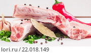 Два сочных куска мяса на кости, стручок красного перца, зелень петрушки и чеснока и лавровый лист. Стоковое фото, фотограф Riasna Yuliia / Фотобанк Лори
