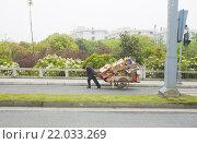 Китаец везет тяжелую тачку с макулатурой по шоссе в гору (2011 год). Редакционное фото, фотограф Владимир Чинин / Фотобанк Лори