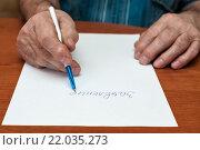 Купить «Мужчина пишет заявление на листке бумаги за столом», эксклюзивное фото № 22035273, снято 3 марта 2016 г. (c) Игорь Низов / Фотобанк Лори