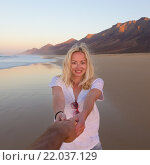 Романтичная пара, взявшись за руки, развлекается на пляже. Стоковое фото, фотограф Matej Kastelic / Фотобанк Лори
