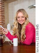 Купить «Pretty woman listening to music and having coffee», фото № 22069845, снято 8 сентября 2015 г. (c) Wavebreak Media / Фотобанк Лори