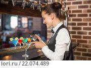 Купить «Barmaid pouring cocktail», фото № 22074489, снято 24 октября 2015 г. (c) Wavebreak Media / Фотобанк Лори