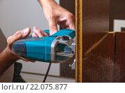 Крепкие мужские руки разрезают мебельный щит лобзиком. Стоковое фото, фотограф Emelinna / Фотобанк Лори