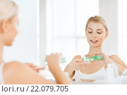 Купить «young woman with lotion washing face at bathroom», фото № 22079705, снято 13 февраля 2016 г. (c) Syda Productions / Фотобанк Лори