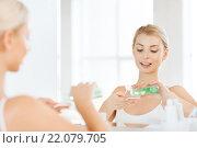 Купить «young woman with lotion washing face at bathroom», фото № 22079705, снято 13 февраля 2016 г. (c) Syda Productions / Фотобанк Лори