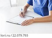 Купить «close up of doctor or nurse writing to clipboard», фото № 22079793, снято 14 марта 2015 г. (c) Syda Productions / Фотобанк Лори