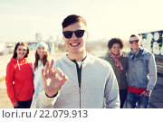 Купить «happy teenage friends showing ok sign on street», фото № 22079913, снято 19 марта 2015 г. (c) Syda Productions / Фотобанк Лори