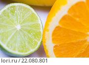 Купить «close up of fresh juicy orange and lime», фото № 22080801, снято 26 апреля 2015 г. (c) Syda Productions / Фотобанк Лори